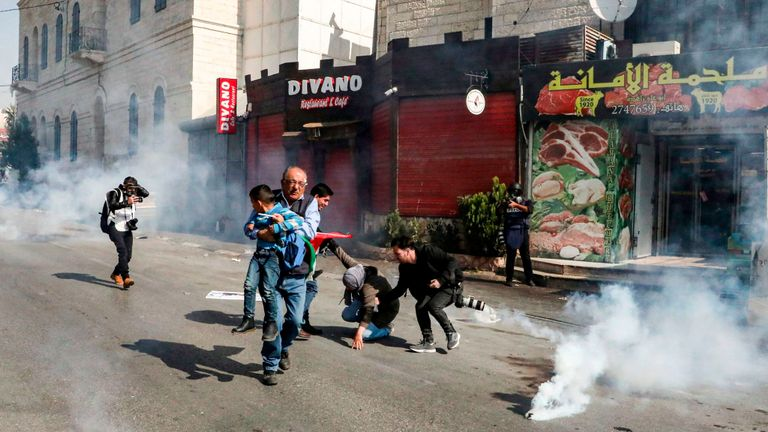 A Palestinian journalist carries away a child as other photojournalists assist a falling woman as they walk amidst tear gas canisters