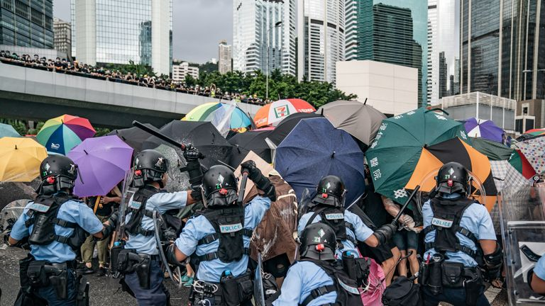 HONG KONG, HONG KONG - JULY 1: Police officers use baton to disperse anti-extradition protesters during a clash outside the Legislative Council Complex ahead of the annual flag raising ceremony of 22nd anniversary of the city's handover from Britain to China on July 1, 2019 in Hong Kong, China. Pro-democracy demonstrators in Hong Kong have organized rallies over the past weeks, calling for the withdrawal of a controversial extradition bill, the resignation of the territory's chief executive Carrie Lam, an investigation into police brutality, and drop riot charges against peaceful protesters. (Photo by Anthony Kwan/Getty Images)