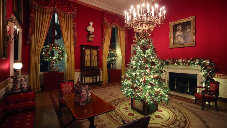 A small decorated Christmas tree stands in the Red Room
