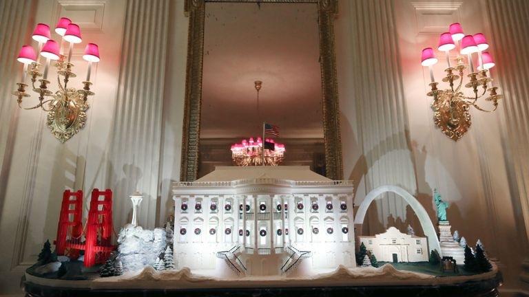 A miniature Golden Gate Bridge and St Louis Gateway Arch stand next to a gingerbread White House in the State Dining Room