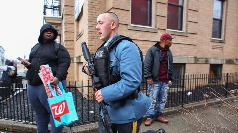 Police officers arrive at the scene of an active shooter in Jersey City, New Jersey, on December 10, 2019. - One officer was shot when two gunmen with a long rifle opened fire in Jersey City, New Jersey, on the afternoon of December 10, 2019 , according to two officials. Two suspects were barricaded in a convenience store, the officials said. One officer was being taken to a nearby hospital. (Photo by Kena Betancur / AFP) (Photo by KENA BETANCUR/Afp/AFP via Getty Images)