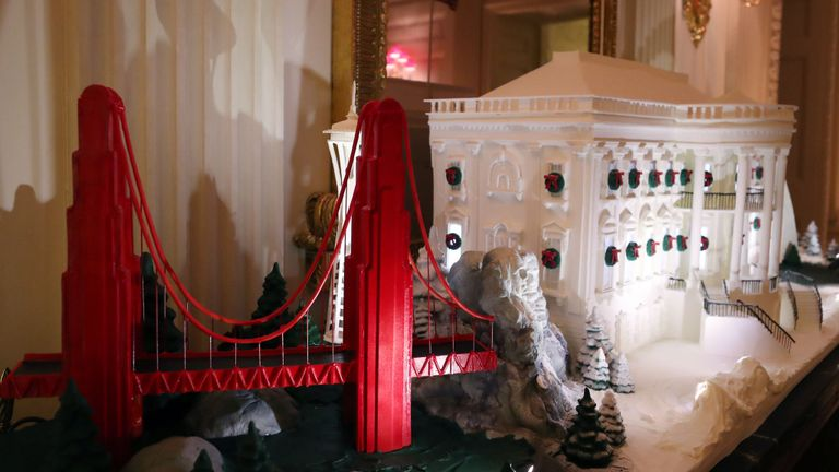A miniature Golden Gate Bridge stands next to a gingerbread White House in the State Dining Room