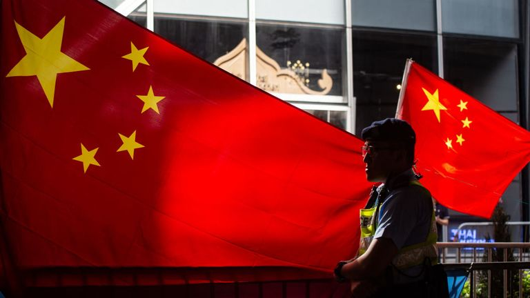 A police officer stands guard in front of Chinese flags as pro-Beijing demonstrators hold a counter-rally during a protest march in Hong Kong on July 1, 2018, to coincide with the 21st anniversary of the city's handover from British to Chinese rule. (Photo by Philip FONG / AFP) (Photo credit should read PHILIP FONG/AFP via Getty Images)